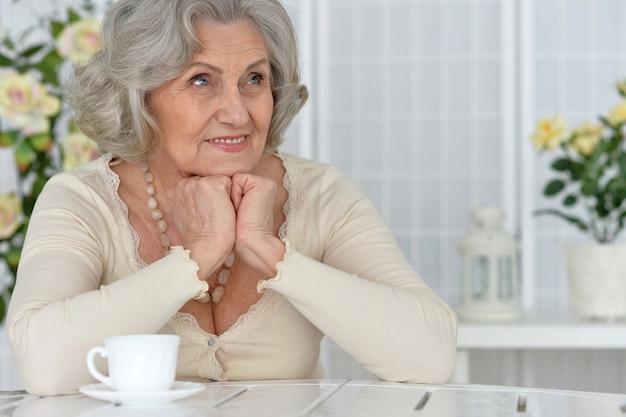 차 컵과 함께 테이블에 행복 한 고위 여자 초상화