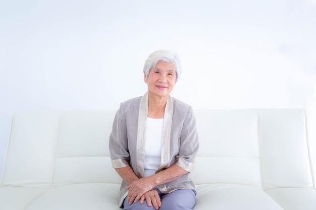 リビングルームの自宅のソファでリラックスして幸せな年配の女性。