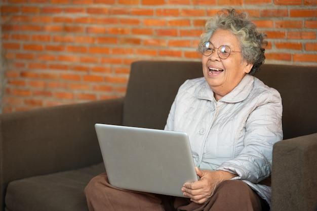 リビングルームのソファーに座っている幸せな年配の女性は、ラップトップ、近代的な技術の概念を使用して古い世代を使用します。