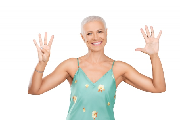 Happy senior woman showing number 45 with her fingers