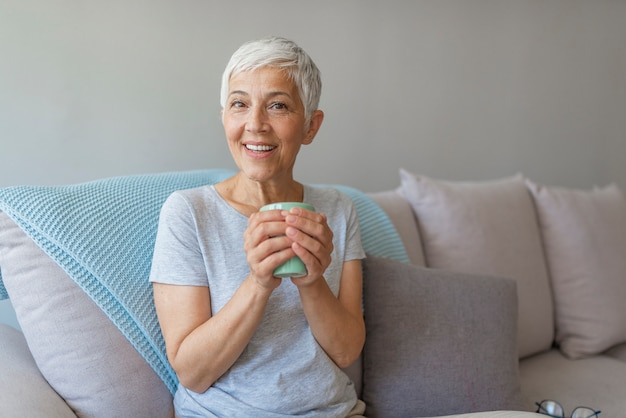 Happy senior woman sitting on a couch while she is drinking a cup of coffee.