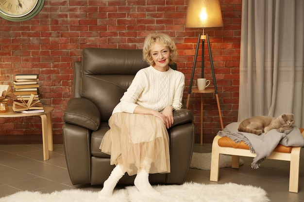 Счастливая старшая женщина, сидящая в кресле у себя дома