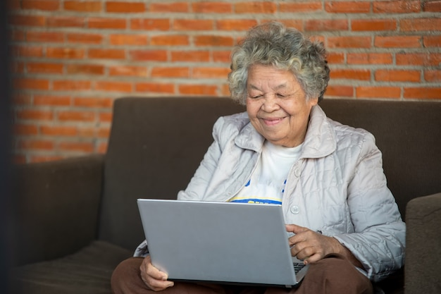 Happy senior woman sitting using computer laptop for spending leisure time on the couch at home.