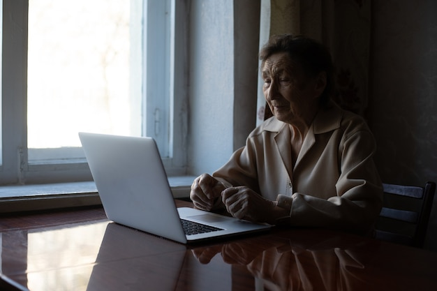 Happy senior woman sitting with her granddaughter looking at laptop making video call. mature lady talking to webcam, doing online chat at home during self isolation. family time during corona