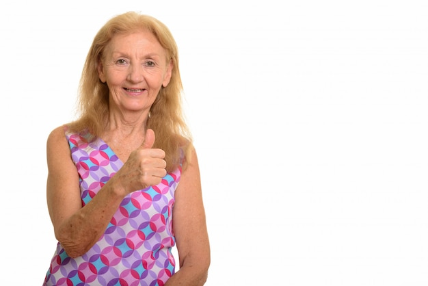 Happy senior woman smiling and giving thumb up