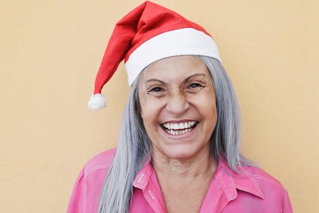 クリスマスの時期にサンタクロースの帽子をかぶってカメラに笑みを浮かべて幸せな年配の女性-顔に焦点を当てる
