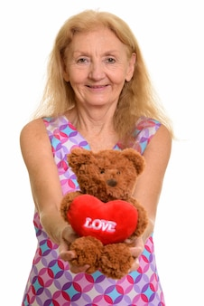 Happy senior woman smiling while giving teddy bear