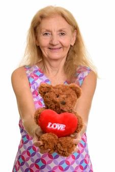 Счастливый старший женщина улыбается, давая плюшевого мишку