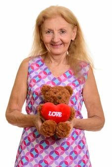 Счастливый старший женщина, улыбаясь во время проведения плюшевого мишку
