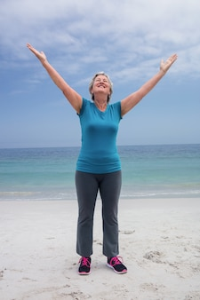 Happy senior woman standing on the beach