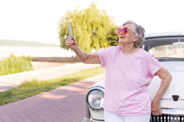 Felice donna anziana in piedi accanto alla sua auto