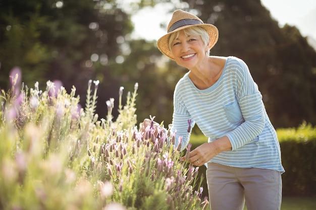 Счастливая старшая женщина стоя в заднем дворе