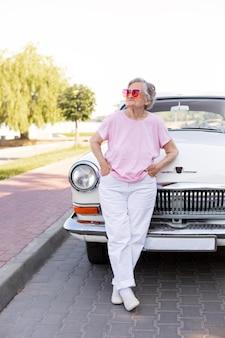 彼女の車の横に立っている幸せな年配の女性 無料写真