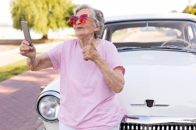 그녀의 차 옆에 서 있는 행복 한 고위 여자