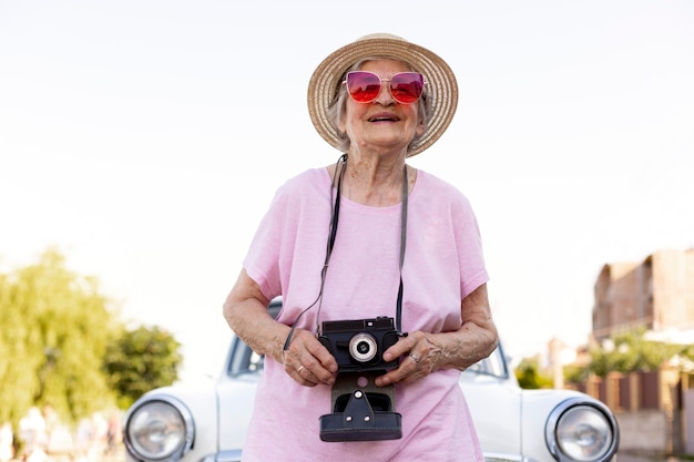 그녀의 차 옆에 서 있는 행복 한 고위 여자 무료 사진