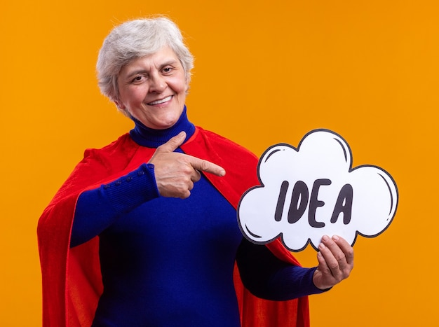 Happy senior woman superhero wearing red cape holding speech bubble sign with word idea pointing with index finger at it smiling cheerfully