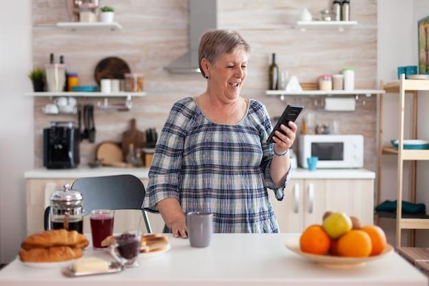 朝食を食べているキッチンでスマートフォンを使用してビデオ会議中に話している幸せな年配の女性。インターネットオンラインチャット技術ビデオウェブカメラを使用してビデオ通話接続カメラを作成している高齢者