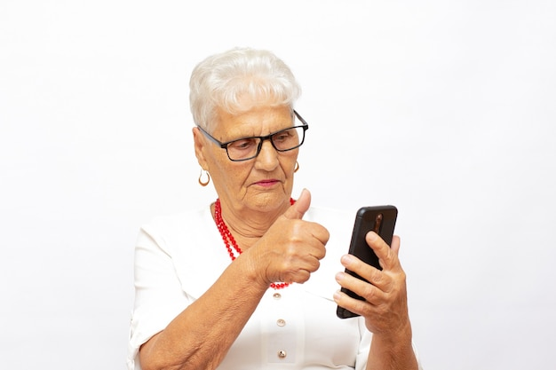 白で隔離の携帯電話で話している幸せな年配の女性