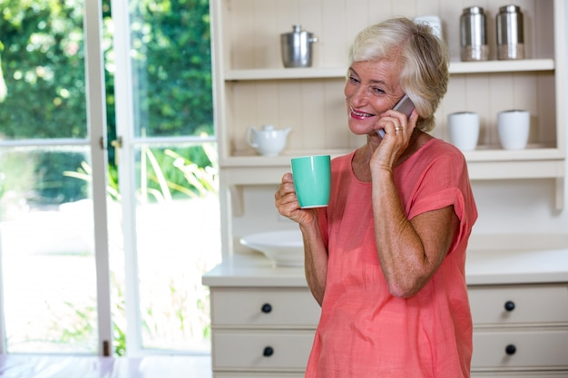 Happy senior woman talking on phone while having coffee in kitchen