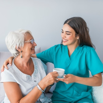 Happy senior woman talking with friendly nurse at geriatric ward