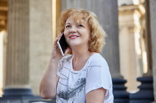Счастливый старший женщина разговаривает по мобильному телефону на открытом воздухе