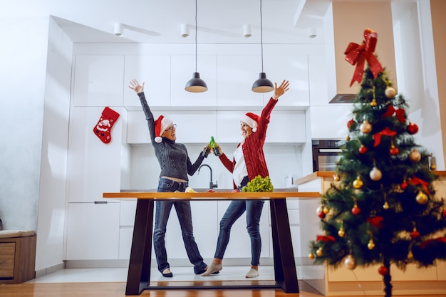 Happy senior woman toasting with beer with her daughter while standing in kitchen. both having santa hats on heads.