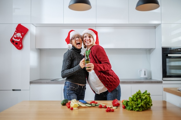 Happy senior woman toasting with beer with her pregnant daughter while standing in kitchen. both having santa hats on heads.