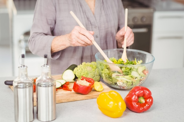 Happy senior woman tossing salad while is standing in kitchen