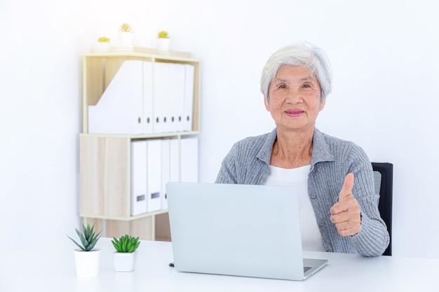 家でラップトップを使用して幸せな年配の女性。テクノロジーと高齢者の概念。
