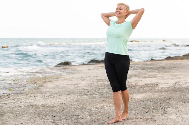 해변에 산책하는 행복 한 고위 여자.