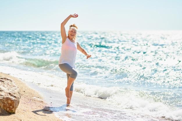 행복 한 고위 여자는 바다로 산책.