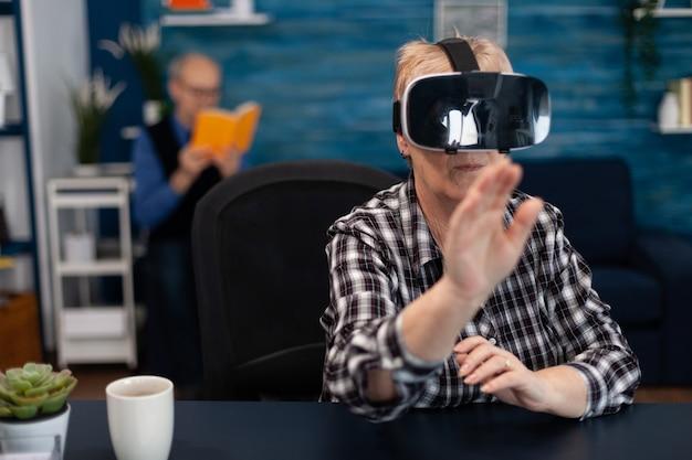 Happy senior woman wearing virtual reality headset