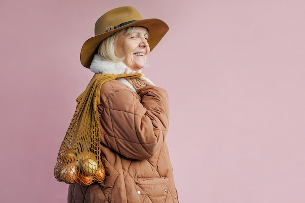 가방 양파와 함께 행복 한 고위 여자입니다. 면 자루를 들고 세련된 겉옷에 기쁜 노인 여성