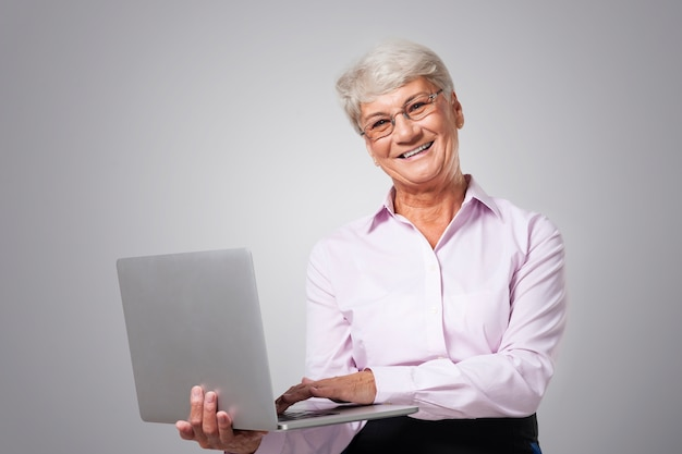 Felice donna senior con laptop contemporaneo