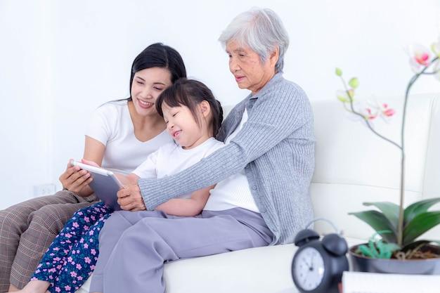 딸과 손녀가 집에서 소파에 앉아 사진, 비디오를 보거나 태블릿으로 소셜 네트워크에서 뉴스를 읽는 행복한 노인 여성. 행복한 가족 개념입니다.