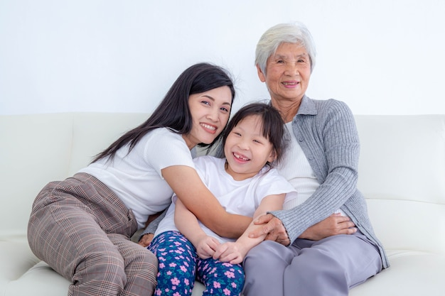 딸과 손녀가 집에서 소파에 앉아 있는 행복한 고위 여성. 행복한 가족 개념입니다.
