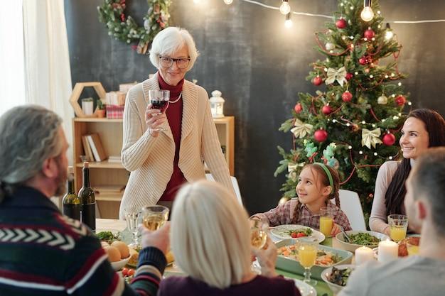 Счастливая старшая женщина с бокалом красного вина делает рождественские тосты, стоя у обслуживаемого стола перед большой семьей