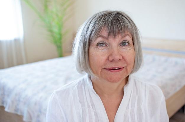 寝室の彼女の家で笑顔でリラックスした白髪の幸せな年配の女性