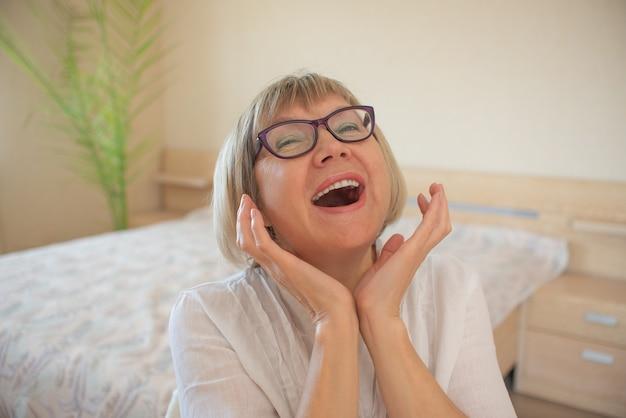 Счастливая старшая женщина с расслабляющей улыбкой седых волос смотрит в камеру в своем доме в спальне.