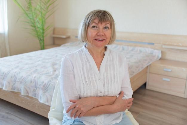 笑顔でリラックスした白髪の幸せな年配の女性が寝室のカメラを見ています