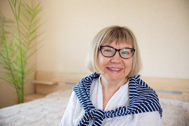 Счастливый старший женщина с седыми волосами с расслабляющей улыбкой в очках смотрит в камеру в своем доме в спальне.