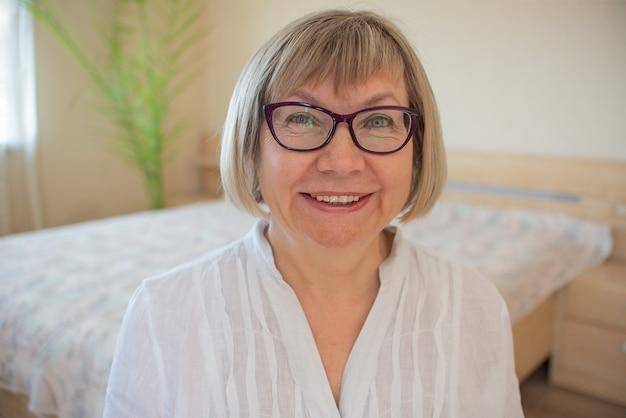 Счастливый старший женщина с седыми волосами с расслабляющей улыбкой в очках смотрит в камеру в своем доме.