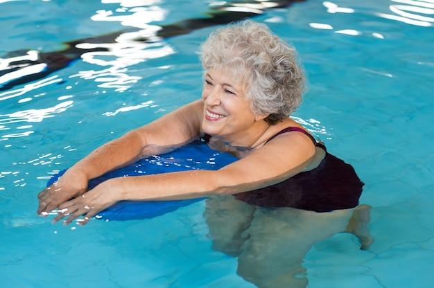 Happy senior woman with kickboard in a swimming pool