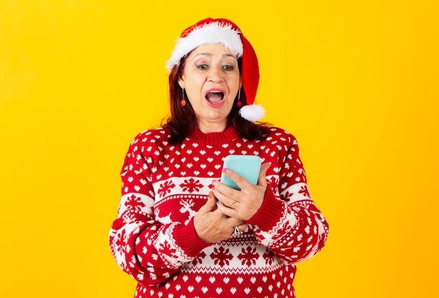 산타 클로스 모자와 함께 행복 한 고위 여자, 휴대폰 보고 놀된