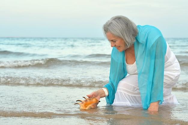 해변에서 셸을 가진 행복 한 고위 여자