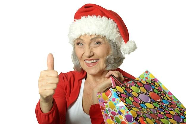 쇼핑백을 들고 엄지손가락을 치켜드는 행복한 노년 여성