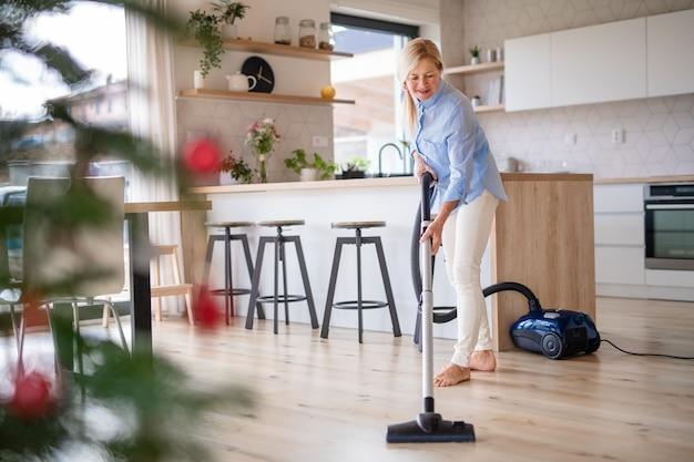 Счастливый старший женщина с пылесосом в помещении дома во время рождества, пылесосить.