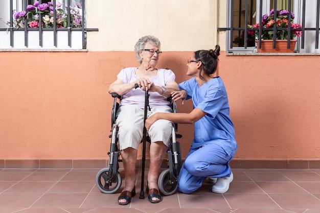 Счастливая старшая женщина с тростью в кресло-коляске с ее попечителем дома
