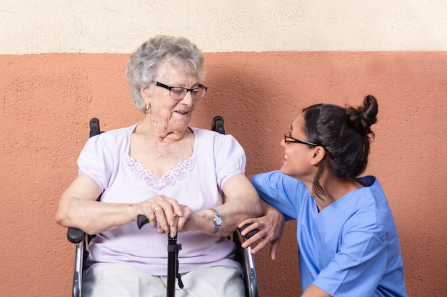 Happy senior woman with walking stick in wheelchair with her caregiver at home