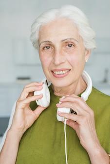 Happy senior woman with white headphone around her neck